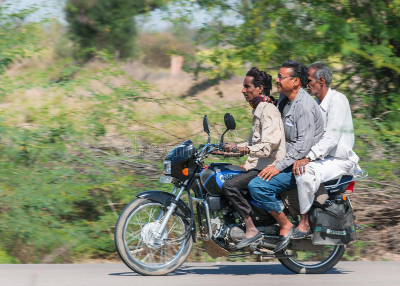 Three generations, riding on one motorbike in India. RAJASTHAN, INDIA - CIRCA FEBRUARY 2011 - Typical view of three guys, actually three generations, riding on stock images