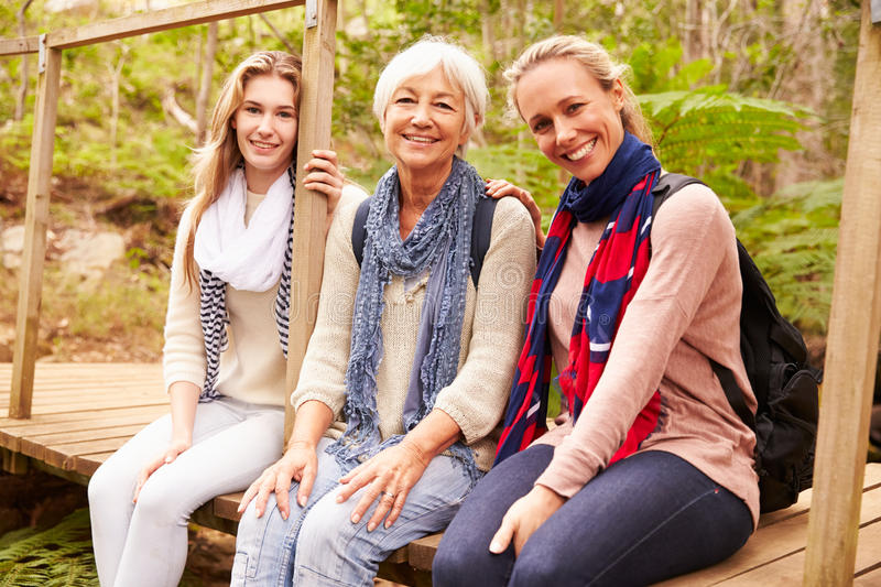Three generations of women sitting in a forest, portrait stock photos
