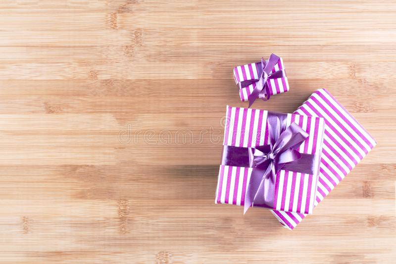 Three gift boxes with purple ribbon on a wooden natural background. royalty free stock photos