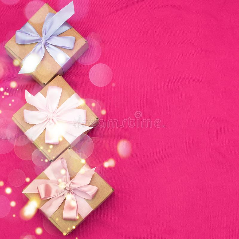Download Three Gift Boxes Tied With Satin Coloured Ribbon On A Pink Background Red Heart