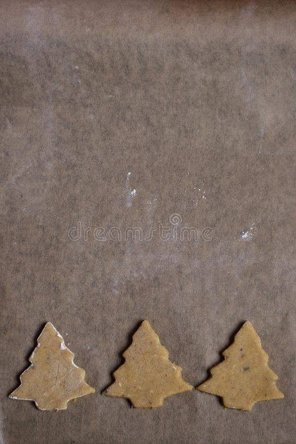 Gingerbread trees lined on baking paper prepared for baking stock photos