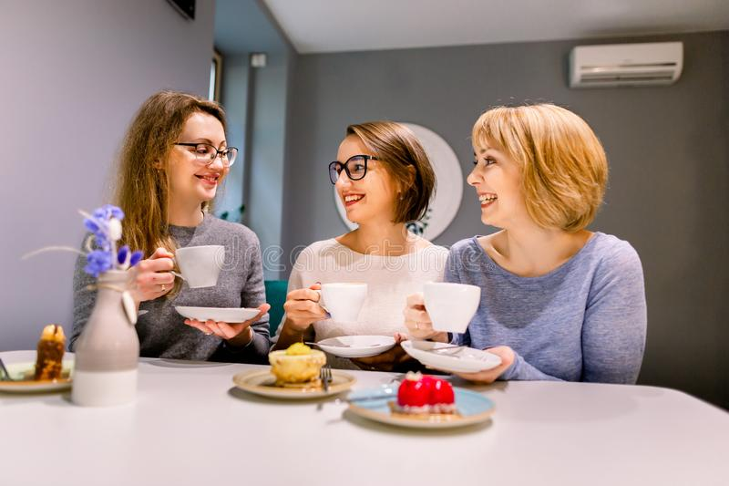Three girl friends drinking coffee and eating desserts cakes in the cafe indoors.  royalty free stock photography