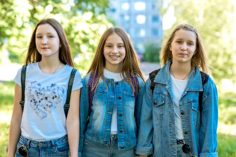 Three girl friends girl schoolgirl. Summer in nature. In jeans clothes behind backpacks. The concept best friends. Three girl friends girl schoolgirl. Summer in stock photography