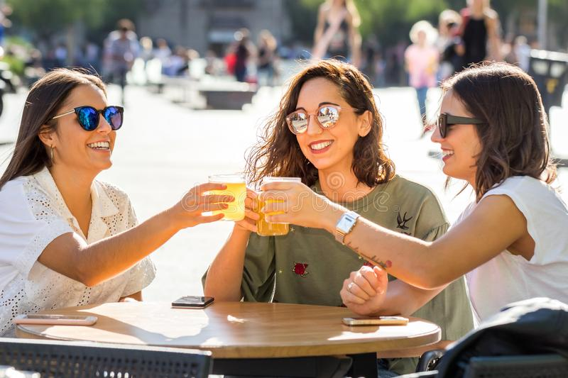 Three girl friends making a toast with drinks on terrace. stock photos