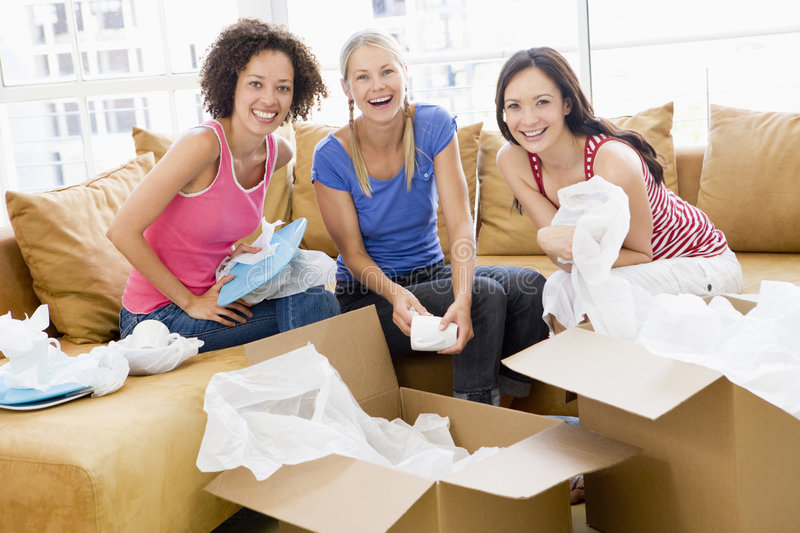 Three girl friends unpacking boxes in new home stock photo