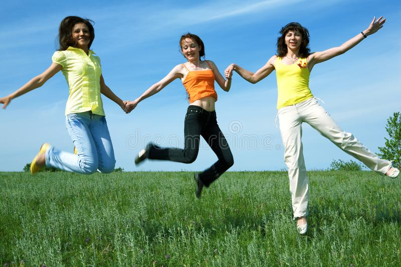 Three girlfriend jump in green field stock image