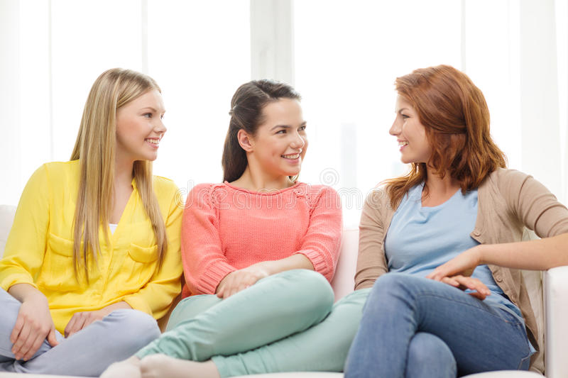 Three girlfriends having a talk at home. Friendship and happiness concept - three girlfriends having a talk at home royalty free stock image