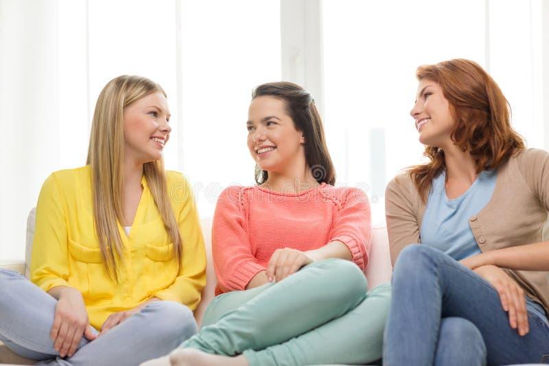 Three girlfriends having a talk at home stock photo