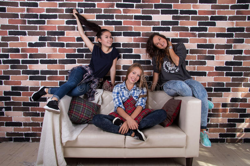 Three girlfriends sitting on the couch and smiling. Three young beautiful girls sitting on the couch and smiling stock image