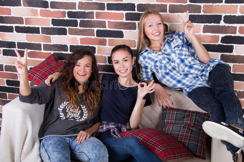 Three girlfriends smiling sitting on the couch. Three young beautiful girlfriends smiling sitting on the couch royalty free stock photography
