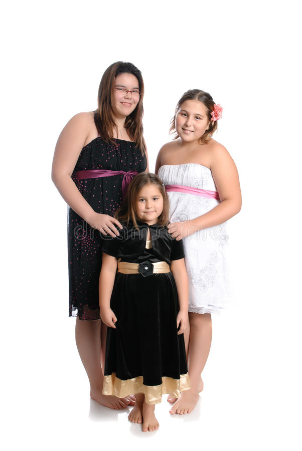 Three Girls. Three young girls of different ages are wearing pretty dresses and are isolated on a white background stock photo