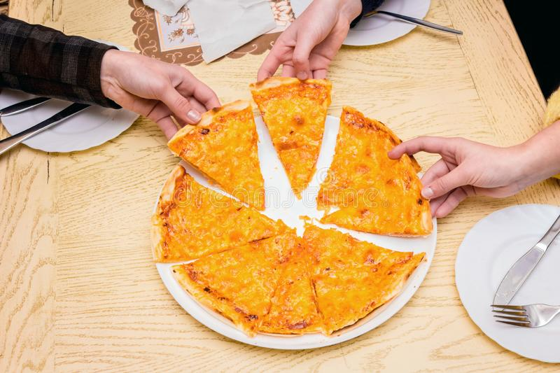 Three girls in a cafe eat pizza. Girls take pizza with hands _. Three girls in a cafe eat pizza. Girls take pizza with hands stock images