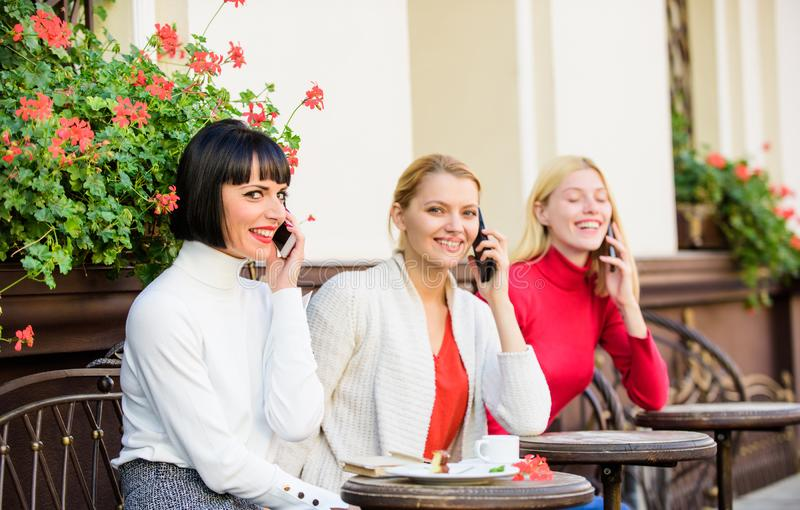 Three girls in cafe speaking on phone. conference call. business meeting at lunch. people connection. modern society stock photo