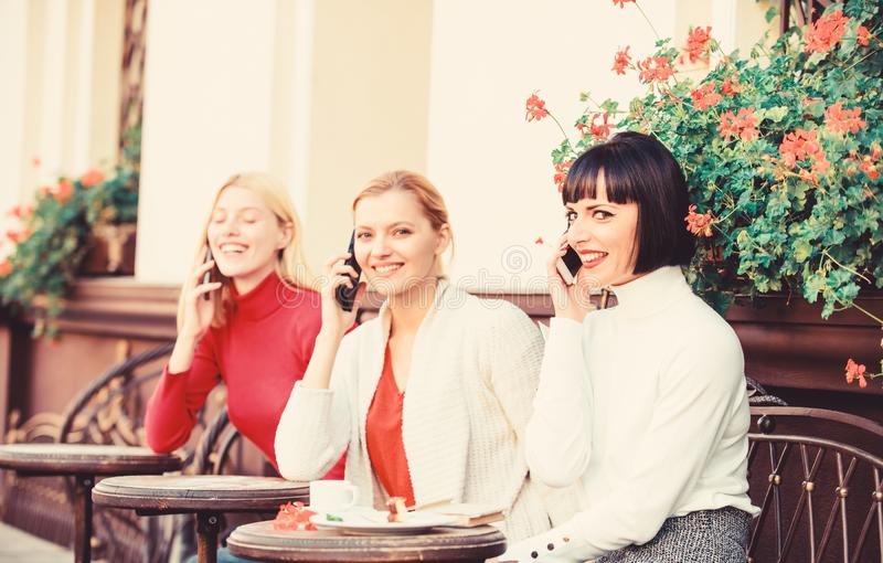 Three girls in cafe speaking on phone. conference call. business meeting at lunch. people connection. modern society stock photography