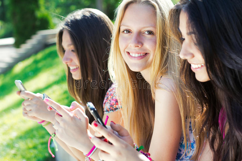 Download Three Girls Chatting With Their Smartphones Stock Image - Image: 33132457