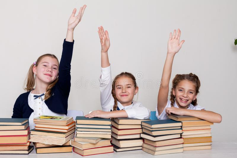 Three girls in the classroom, raised a hand up to answer. Three girls in the classroom, wish to reply pulled a hand up royalty free stock images