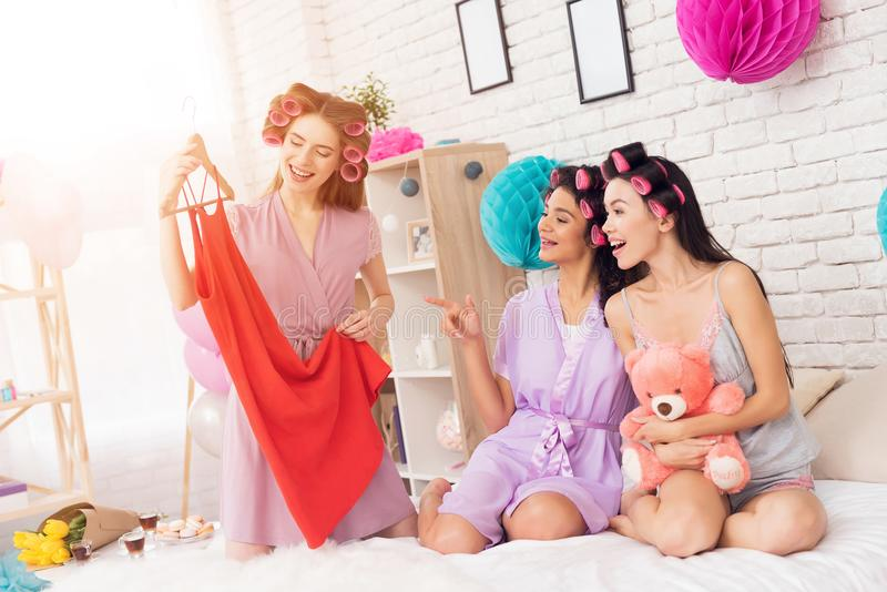 Three girls with curlers in their hair looking at new dress. They are celebrating women`s day March 8. Three girls in robes with curlers in their hair looking stock image