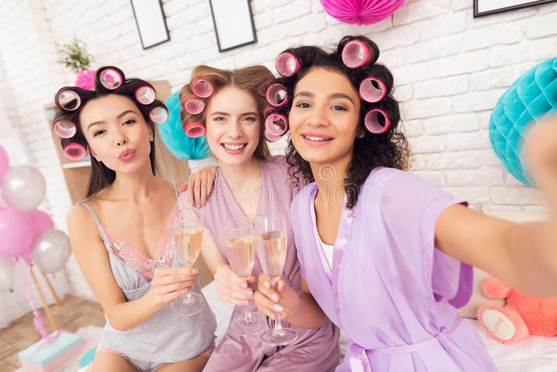 Three girls with curlers in their hair taking selfie. They are celebrating women`s day March 8. Three girls in robes with curlers in their hair taking selfie royalty free stock images