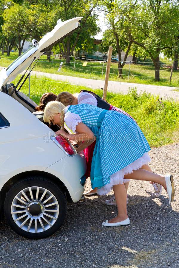 Three Girls In Dirndl Looking In A Car-boot Stock Photography