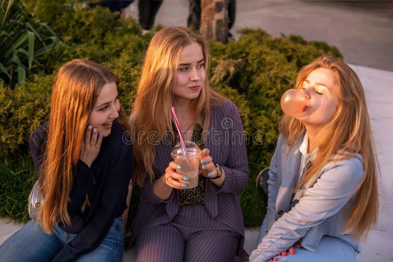 Three girls friends having fun on evening broadway. Eating ice cream, drinking ice fresh milk shake and chewing bubble stock photos