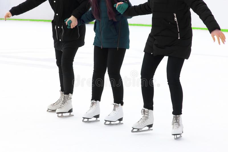 Three girls holding hands ice-skating on the ice rink. Sports, Hobbies and recreation of active people royalty free stock photography