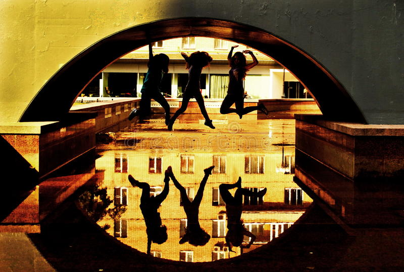 Three girls jump up under the bridge royalty free stock photography