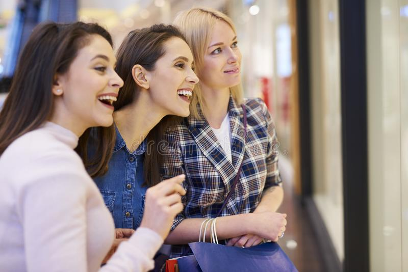 Three girls looking at big window display stock photography