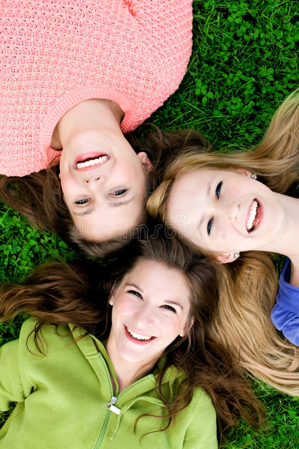 Three girls lying on the grass. And smiling royalty free stock photography