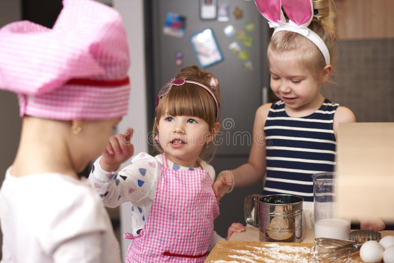 Three girls making a cookies royalty free stock photo