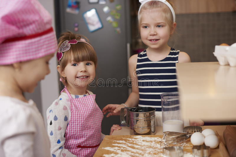 Three girls making a cookies stock image