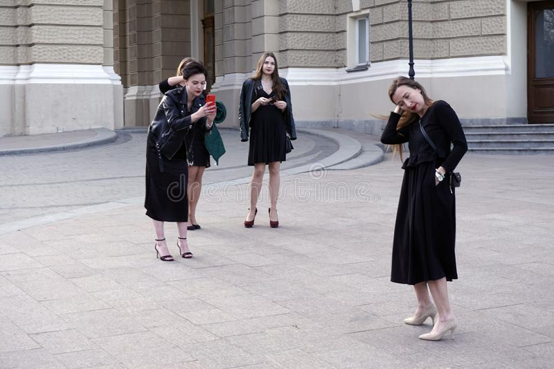Three girls making photos with smartphone of their friend girl in black dresses. Downtown the city royalty free stock images