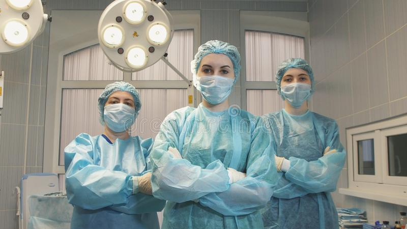 Three girls nurse in the operating room take off the face mask and smile royalty free stock photo