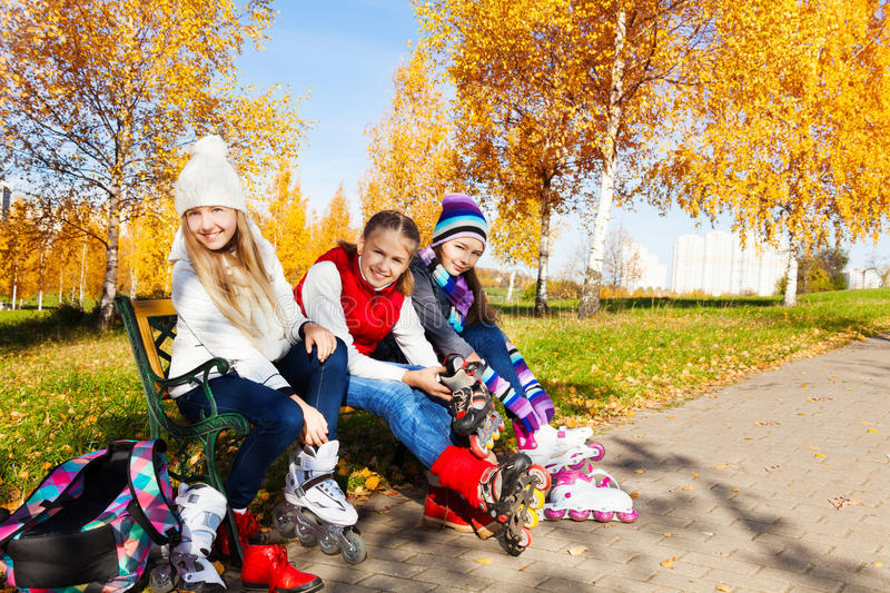 Three girls putting on roller blades in the park stock images