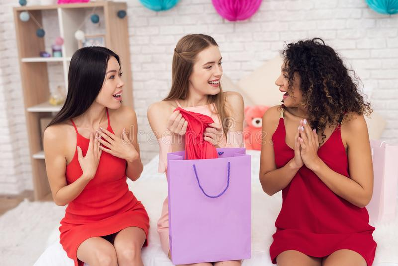 Three girls with shopping bags taking red ress out of bag. They are celebrating women`s day March 8. royalty free stock images