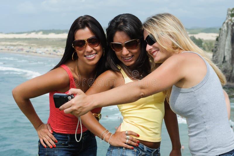 Three beautiful women taking selfie on the beach stock image