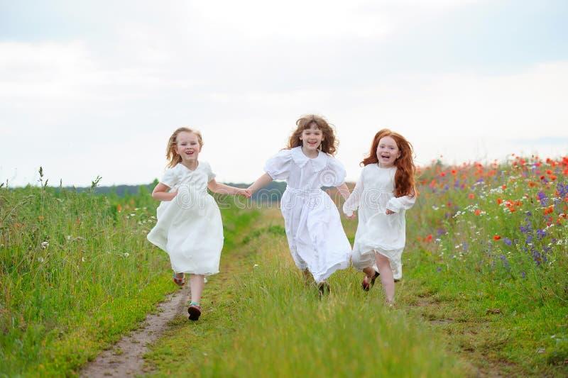 Three girls run approaching. Children playing at fresh air stock photo