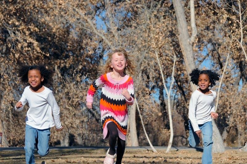 Three girls running stock images