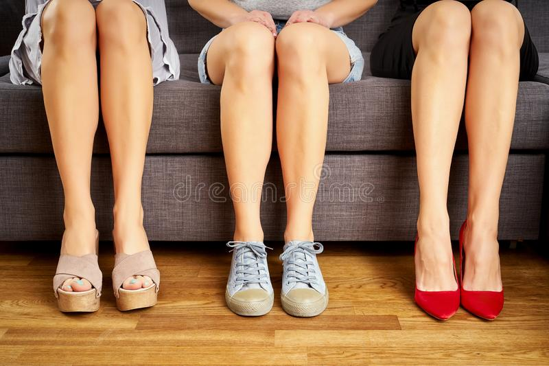Three girls with legs sitting on the couch in different shoes and different styles on couch. royalty free stock image