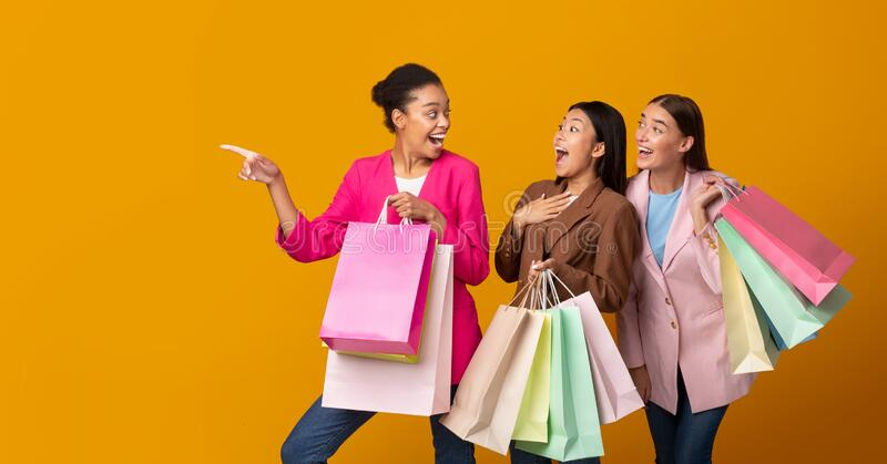 Three Girls On Shopping Holding Bags Pointing Finger, Studio, Panorama royalty free stock photos