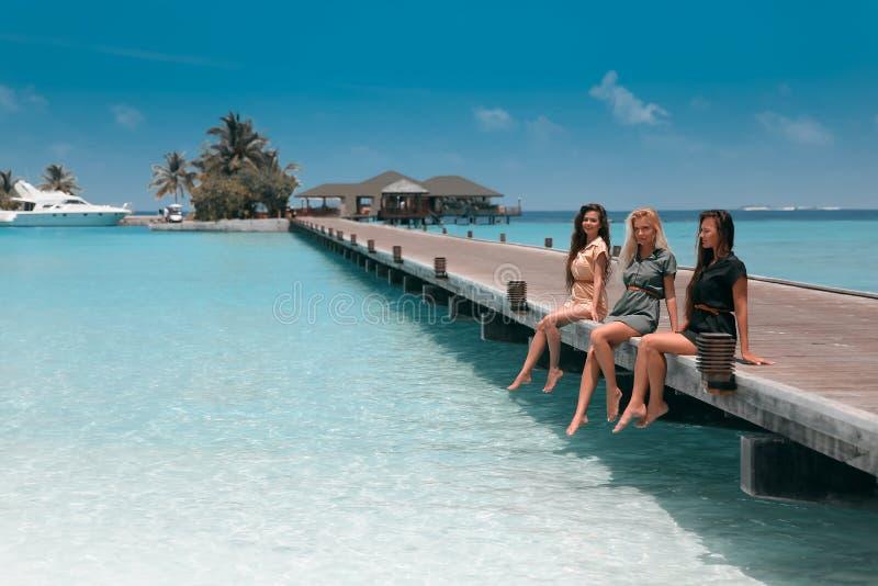 Three girls sitting on wooden planks on tropical beach Maldives. Girlfriends  having fun, pleasure and enjoyment. Slim cute models stock photos