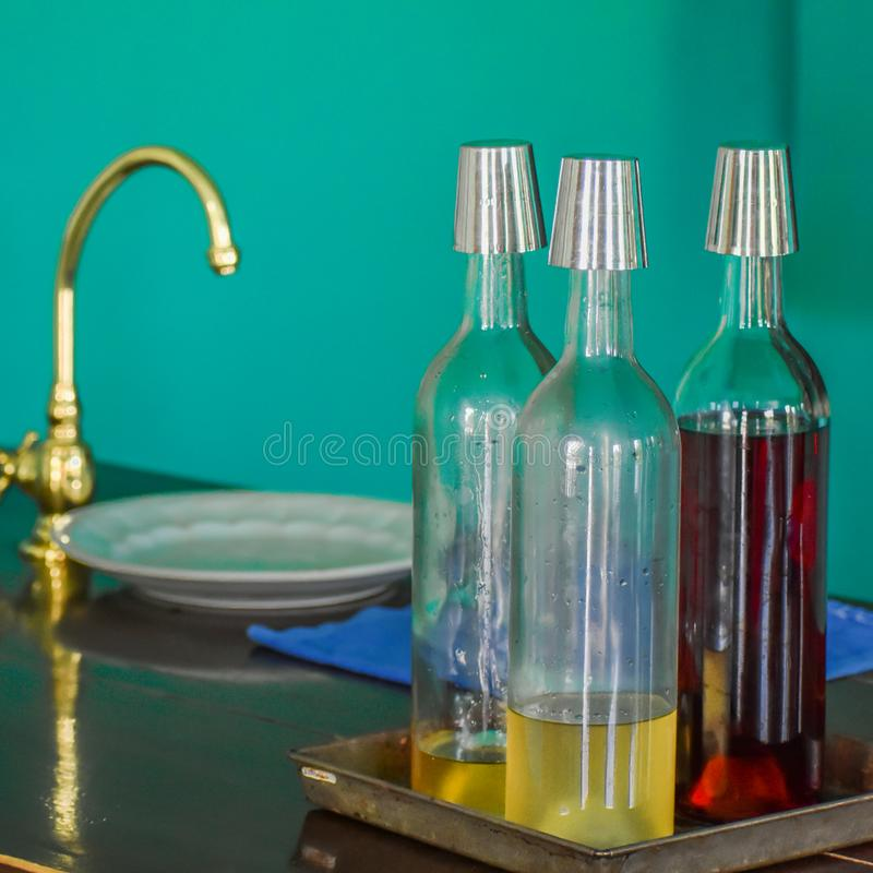 Three Glass Bottles, Gold Sink, Teal Wall stock image