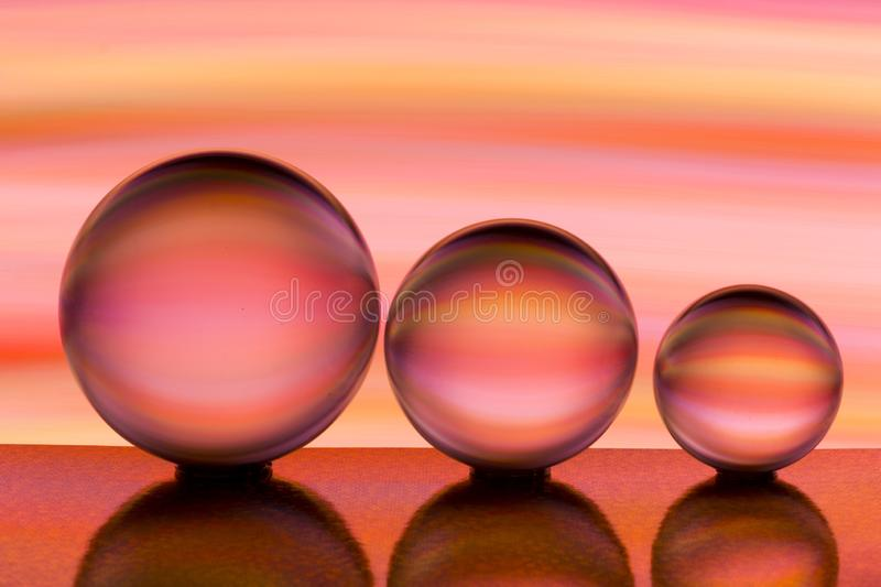 Three glass crystal balls in a row with a rainbow of colorful light painting behind them stock image