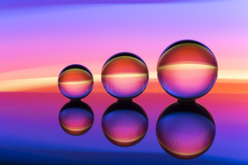 Three glass crystal balls in a row with a rainbow of colorful light painting behind them royalty free stock images