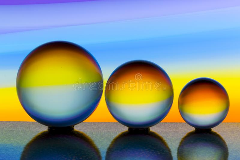 Three glass crystal balls in a row with a rainbow of colorful light painting behind them royalty free stock photo