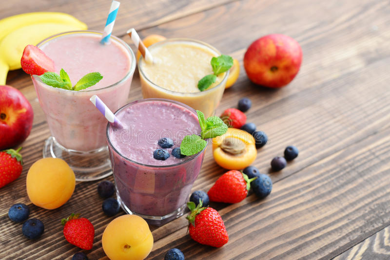 Three glass of fruit milkshakes. Or smoothies with drinking straws and fresh fruits and berries on wooden background stock image