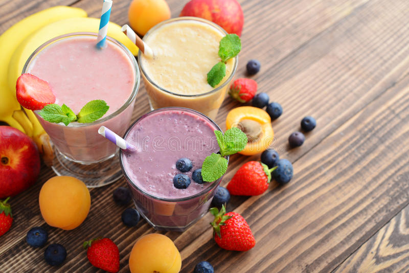 Three glass of fruit milkshakes. Or smoothies with drinking straws and fresh fruits and berries on wooden background royalty free stock image