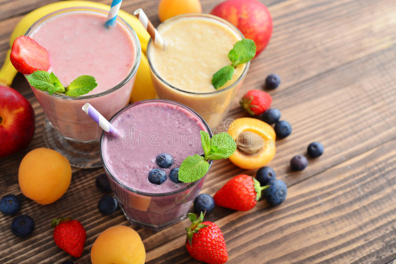 Three glass of fruit milkshakes. Or smoothies with drinking straws and fresh fruits and berries on wooden background royalty free stock photography