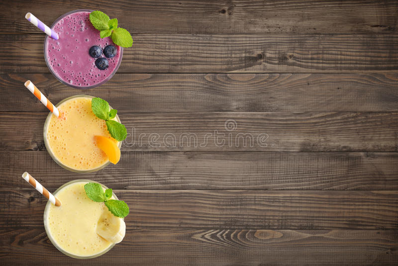 Three glass of fruit milkshakes. Or smoothies with drinking straws and fresh fruits and berries on wooden background, top view royalty free stock photography