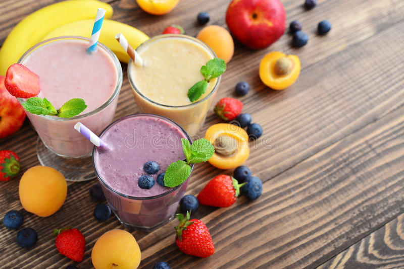 Three glass of fruit milkshakes. Or smoothies with drinking straws and fresh fruits and berries on wooden background, top view royalty free stock photo