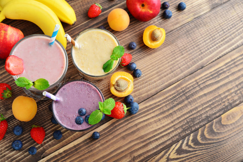 Three glass of fruit milkshakes. Or smoothies with drinking straws and fresh fruits and berries on wooden background, top view stock photo